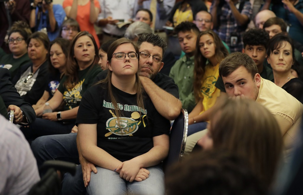 Grace Johnson, a student at Santa Fe High School, center, with her father Steve, and other students, listens during a roundtable discussion in Austin,...