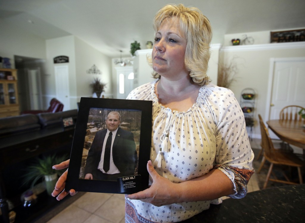 FILE - In this July 13, 2016 file photo, Laurie Holt holds a photograph of her son Josh Holt at her home, in Riverton, Utah.  Josh Holt  has been rele...