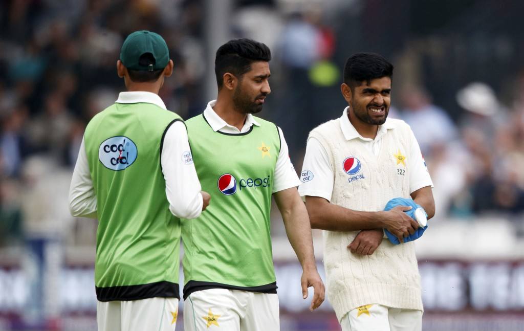 Pakistan's Babar Azam, right, walks off after an injury during day two of the First NatWest Test Series match at Lord's, London, Friday May 25, 2018. ...