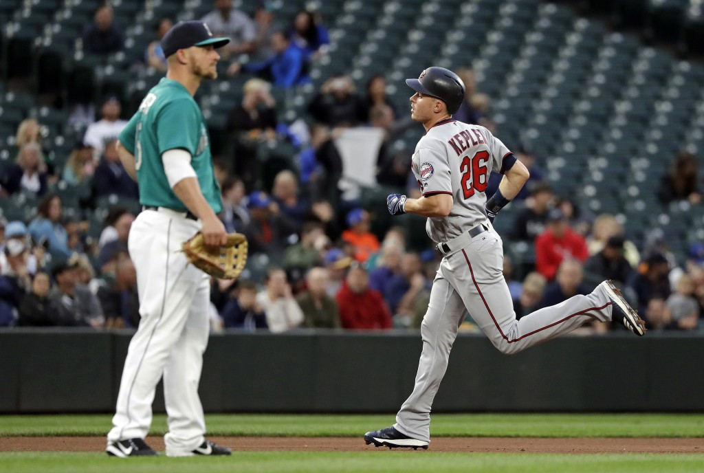 Minnesota Twins' Max Kepler, right, rounds the bases on a home run as Seattle Mariners third baseman Kyle Seager looks away during the fifth inning of...