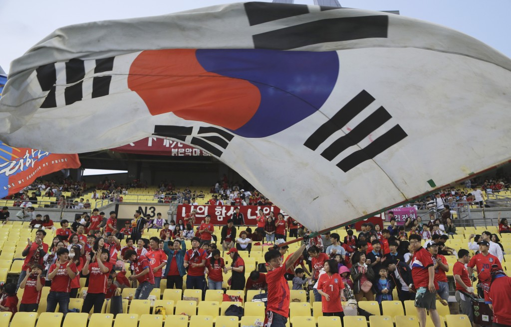 A South Korean soccer fan waves a huge national flag  prior to the start of the international friendly soccer match between South Korea and Honduras, ...