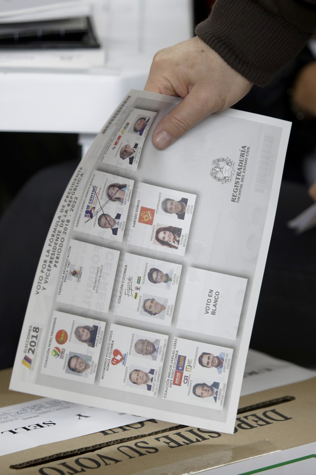 A voter casts his marked ballot for the presidential election in Bogota, Colombia, Sunday, May 27, 2018. (AP Photo/Fernando Vergara)