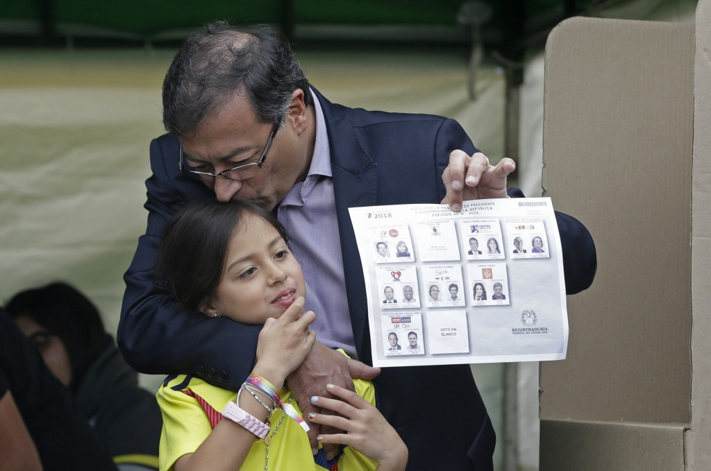 Gustavo Petro, presidential candidate for Colombia Humana, kisses his daughter Antonella as he shows his marked ballot to the press, during the presid...