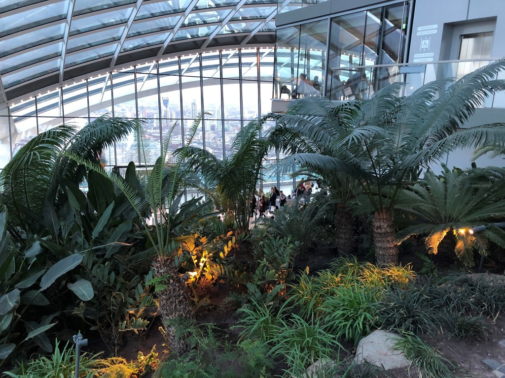 This March 2018 photo shows plants inside Sky Garden with a view of London through the glass. The green space sits atop a 34-story building known as t...