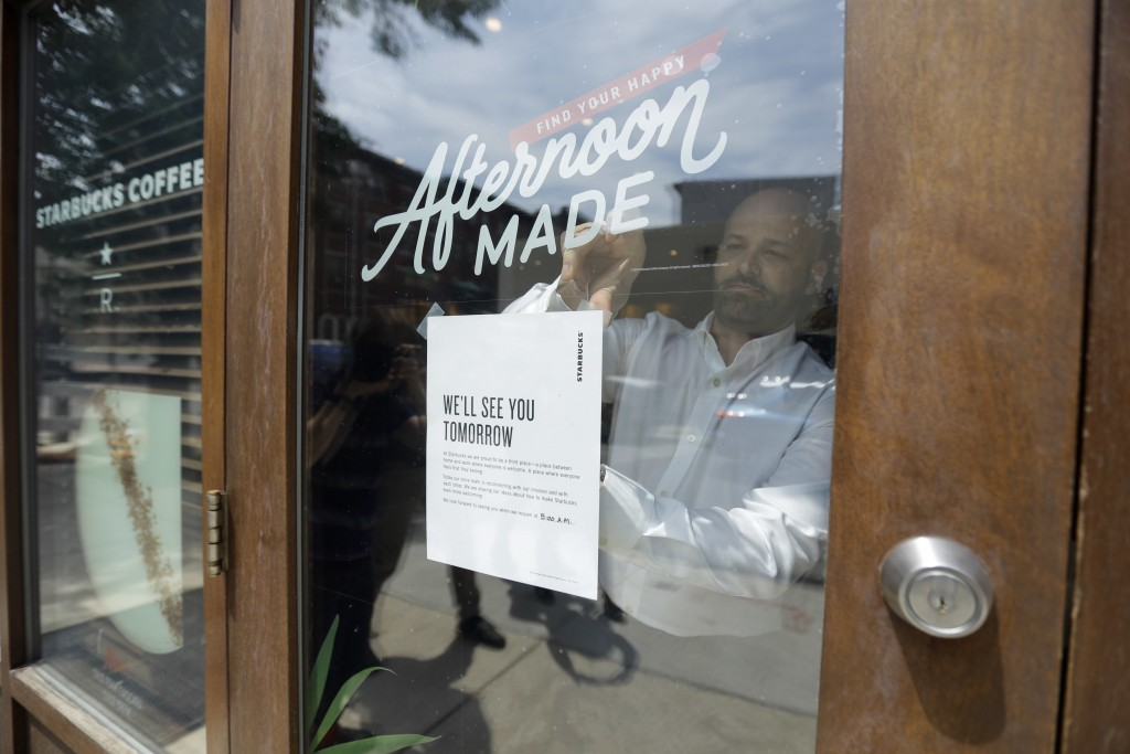 A man tapes a sign to a door at a Starbucks Coffee shop, Tuesday, May 29, 2018, in Philadelphia. After the arrests of two black men, Rashon Nelson and...