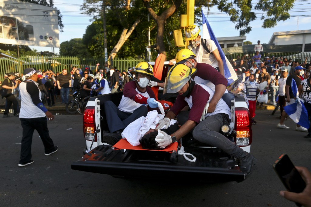 A dead demonstrator who was shot in the head is tended by paramedics after clashes erupted during a march against Nicaragua's President Daniel Ortega ...
