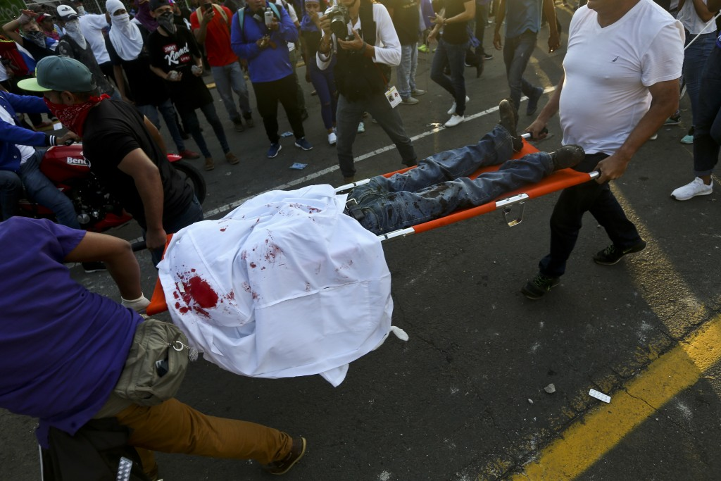 A dead demonstrator who was shot in the head is carried by paramedics after clashes erupted during a march against Nicaragua's President Daniel Ortega...