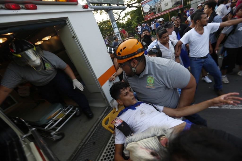 A man who was shot and wounded is loaded into an ambulance during clashes at a march against Nicaragua's President Daniel Ortega in Managua, Nicaragua...