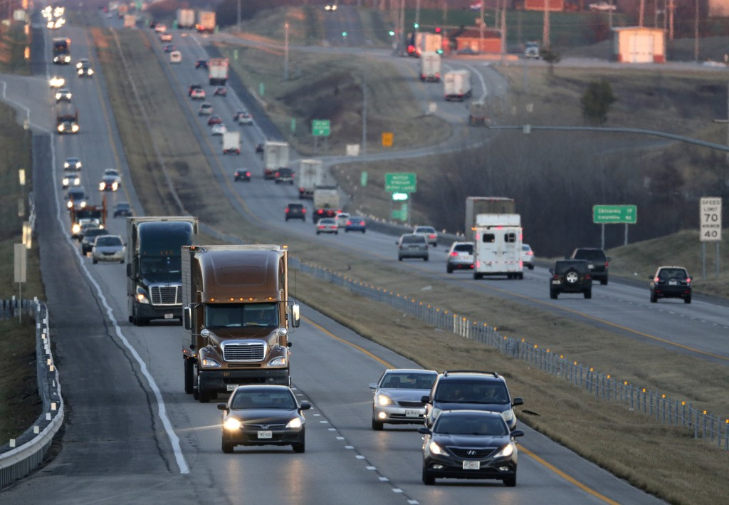FILE - In this Jan. 14, 2016, file photo, vehicles travel along Interstate 70 near Odessa, Mo. Suddenly road trips are trendy again. Surveys from MMGY...