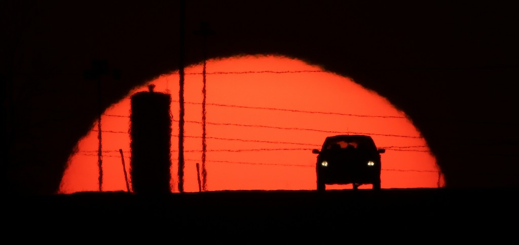 FILE - In this March 27, 2013, file photo, a car is silhouetted against the setting sun as it travels along Interstate 70 in Kansas City, Kan. Suddenl...