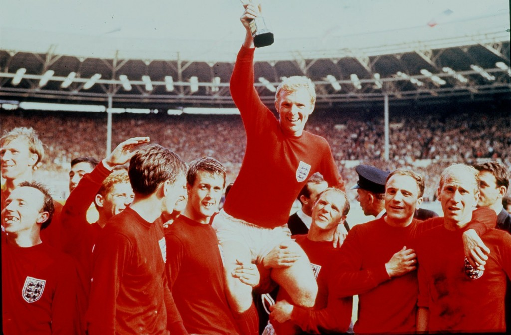 FILE - In this July 30 1966 file photo, England's soccer captain Bobby Moore, carried shoulder high by his teammates, holds aloft the Jules Rimet Trop...