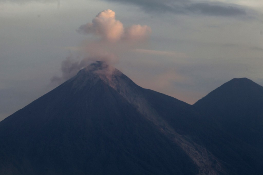 Volcan de Fuego, or Volcano of Fire, blows outs a cloud of ash, as seen from Escuintla, Guatemala, Tuesday, June 5, 2018. at right inactive Acatenango...