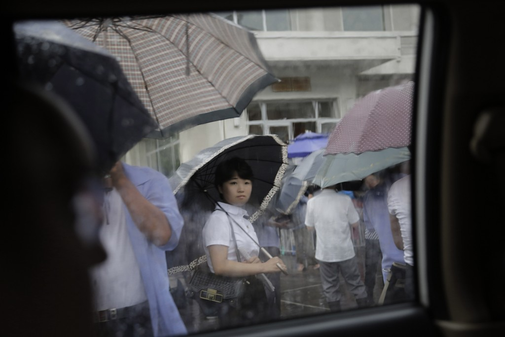 FILE - A woman waits in the rain outside a restaurant in Pyongyang, North Korea, on July 25, 2015. The rainy season in North Korea usually lasts throu...