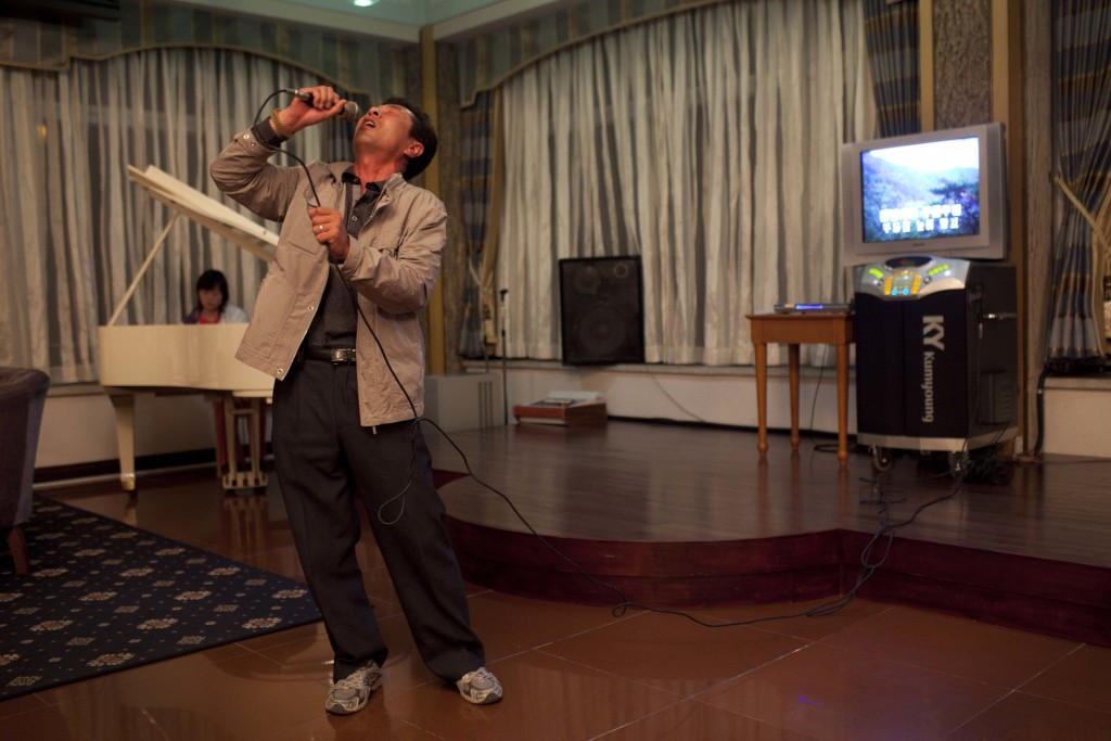 FILE - A man sings karaoke while his daughter plays piano at a hotel bar in Mount Kumgang, North Korea, on Oct. 7, 2011. (AP Photo/David Guttenfelder,...