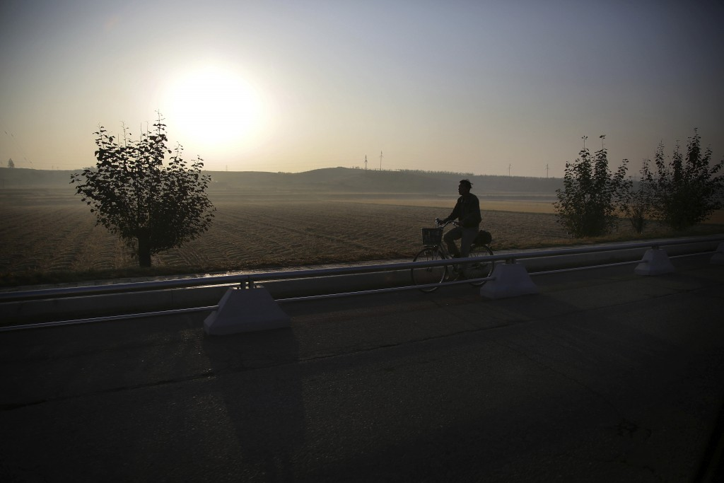 FILE - A man cycles past rice fields in Pyongyang, North Korea, in the early morning on Oct. 13, 2015. (AP Photo/Wong Maye-E, File)