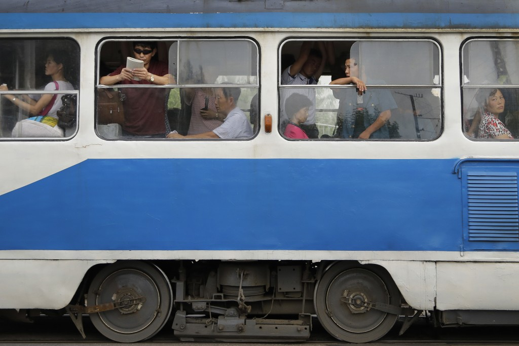 FILE - Commuters ride an electric trolley in downtown Pyongyang, North Korea, at the end of a work day on July 28, 2017. (AP Photo/Wong Maye-E, File)