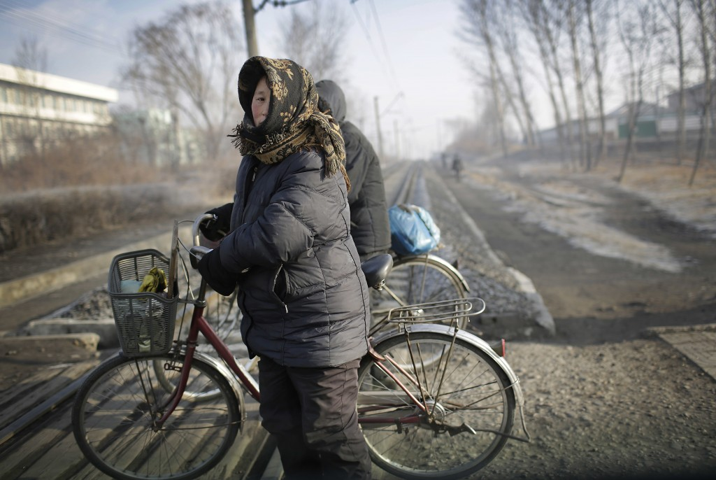 FILE - Women push their bicycles across a train track in the Chollima district of Nampo, a city and seaport located on the west coast of North Korea, ...