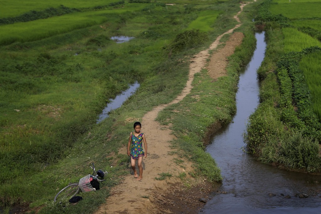 FILE - A young girl dressed in her swimming suit walks along a stream between fields in Hamju, North Korea, on July 20, 2017. (AP Photo/Wong Maye-E, F...