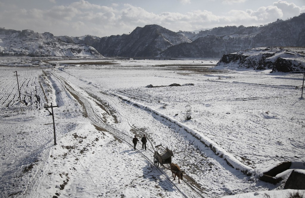 FILE - Two farmers walk between snow-covered fields on Dec. 3, 2015, in Kujang county in North Pyongan, North Korea, where the winter season has begun...
