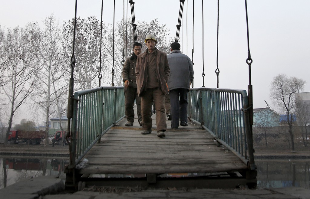 FILE - Construction workers walk on a bridge that takes them over the Pothong River in Pyongyang, North Korea, on Nov. 28, 2015. The Pothong River is ...
