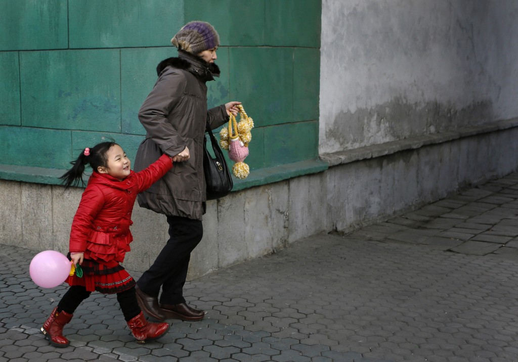 FILE - A girl walks with her mother on a downtown street in Pyongyang, North Korea, on Feb.18, 2014. (AP Photo/Vincent Yu, File)