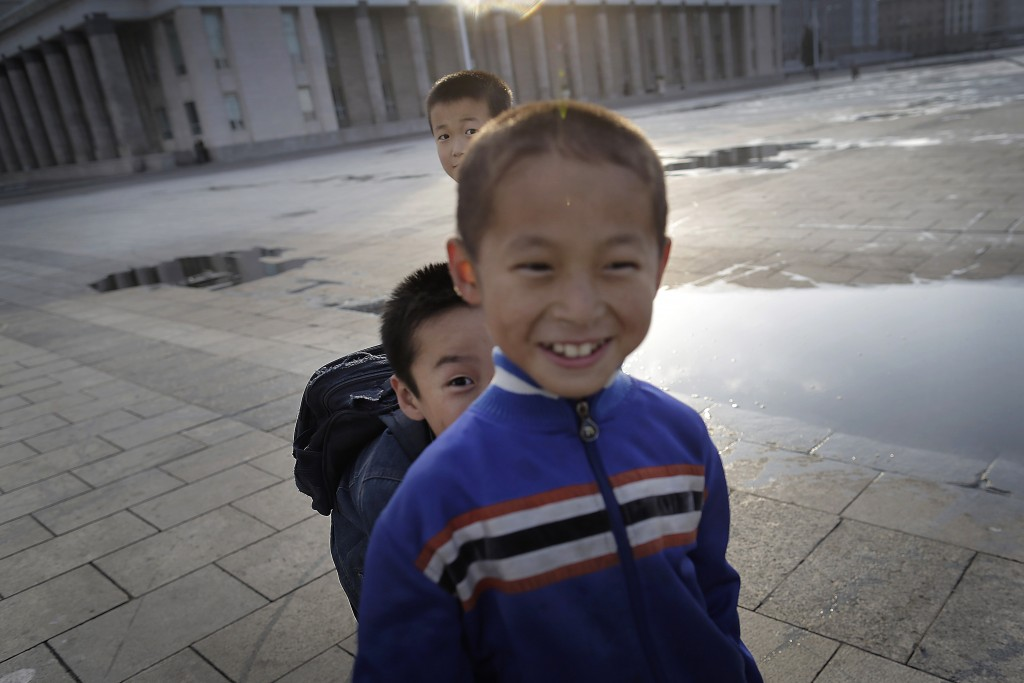 FILE - Children break into laughter as they try to hide from and catch one another while rollerblading at Kim Il Sung Square in Pyongyang, North Korea...