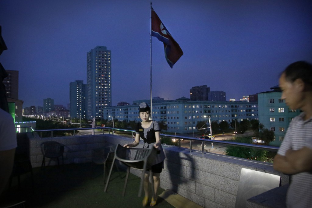 FILE - A waitress moves a dining chair at a restaurant terrace that overlooks a residential street at dusk in Pyongyang, North Korea, on June 19, 2017...
