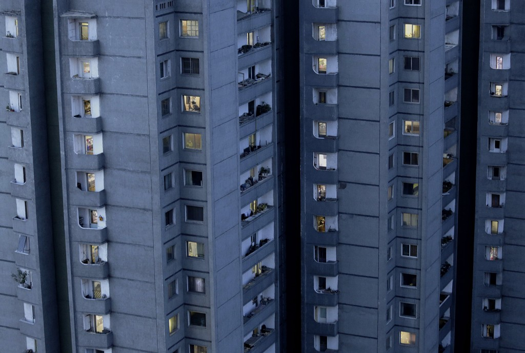 FILE - Lights are switched on in occupied apartments as dusk descends in Pyongyang, North Korea, on May 10, 2015. Most of the North Koreans in Pyongya...
