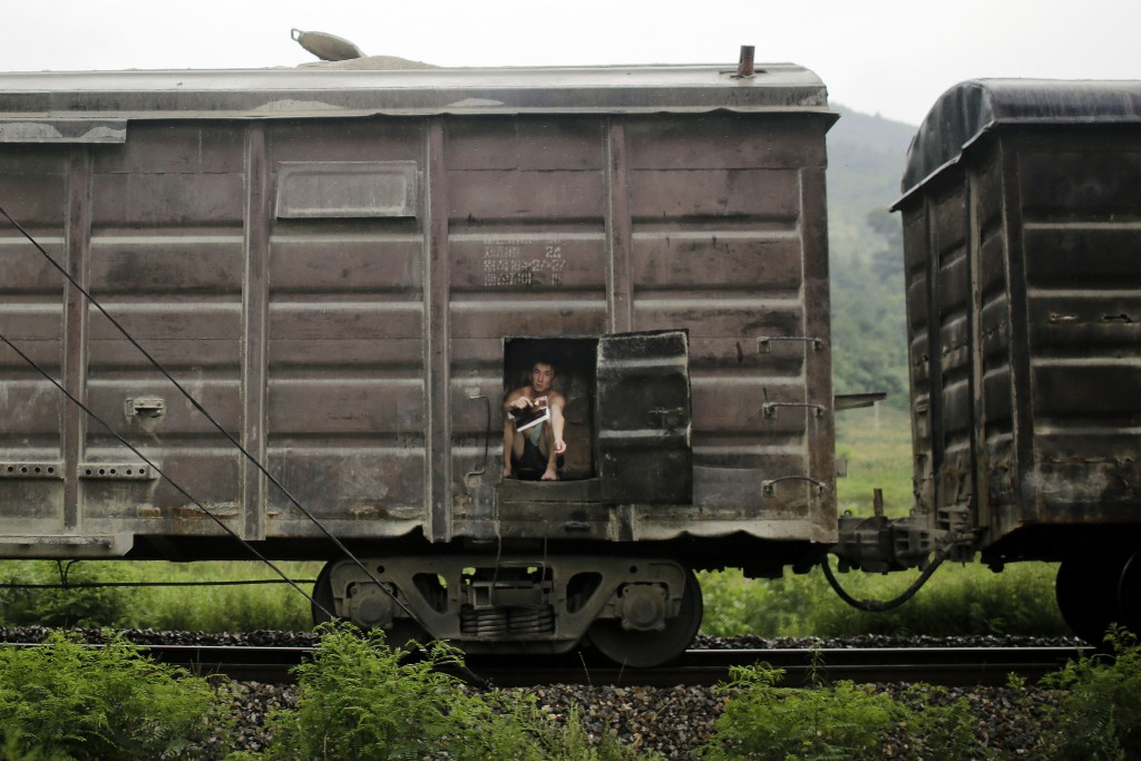 FILE - A man sits in the car of a cargo train traveling toward Pyongyang along the outskirts of Hamhung, North Korea, on July 21, 2017. (AP Photo/Wong...