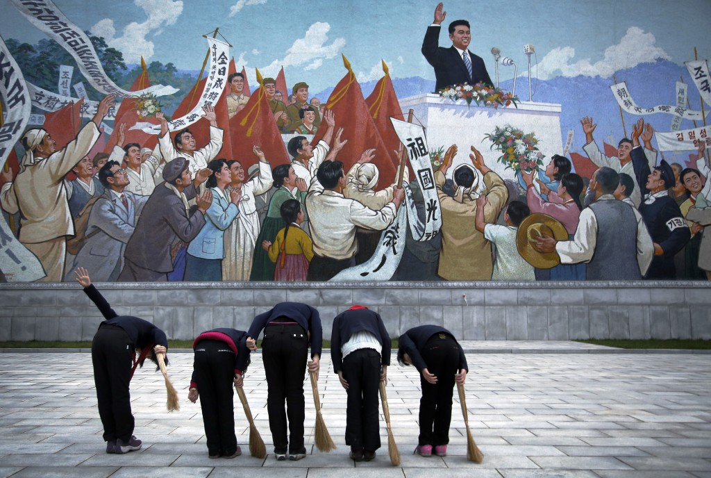 FILE - School girls holding brooms bow to pay their respects toward a mural that depicts the late North Korean leader Kim Il Sung delivering a speech,...