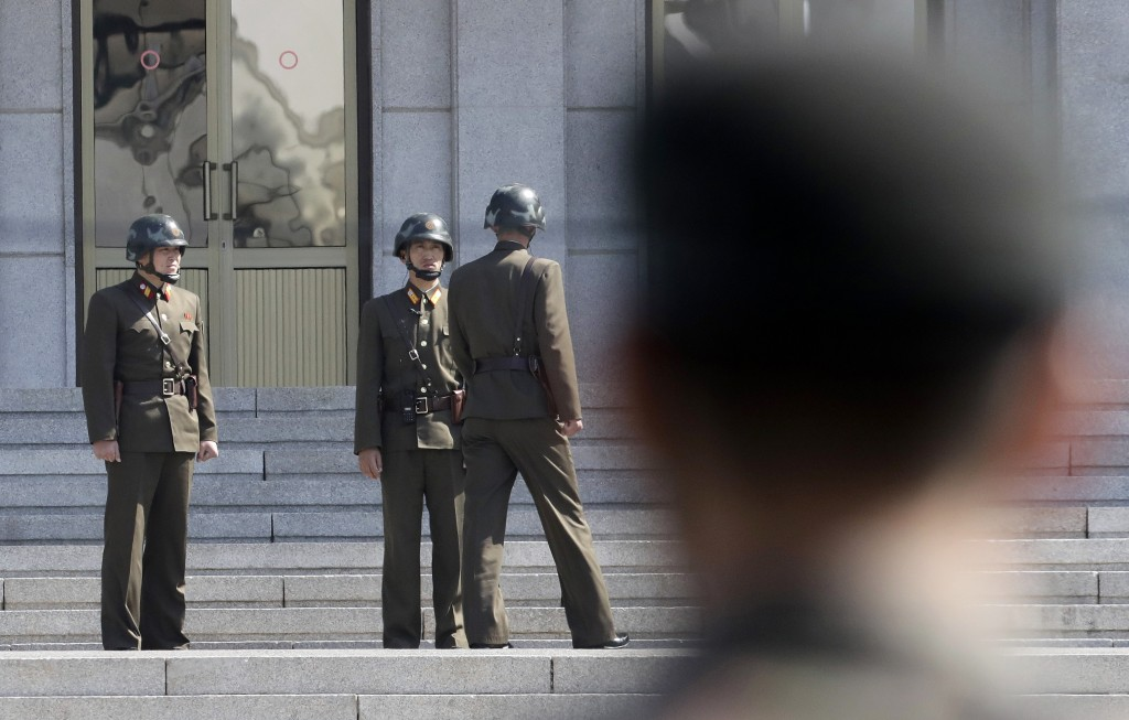 FILE - In this April 18, 2018 file photo, three North Korean soldiers talk each others as a South Korean soldier, right, stands at the border village ...