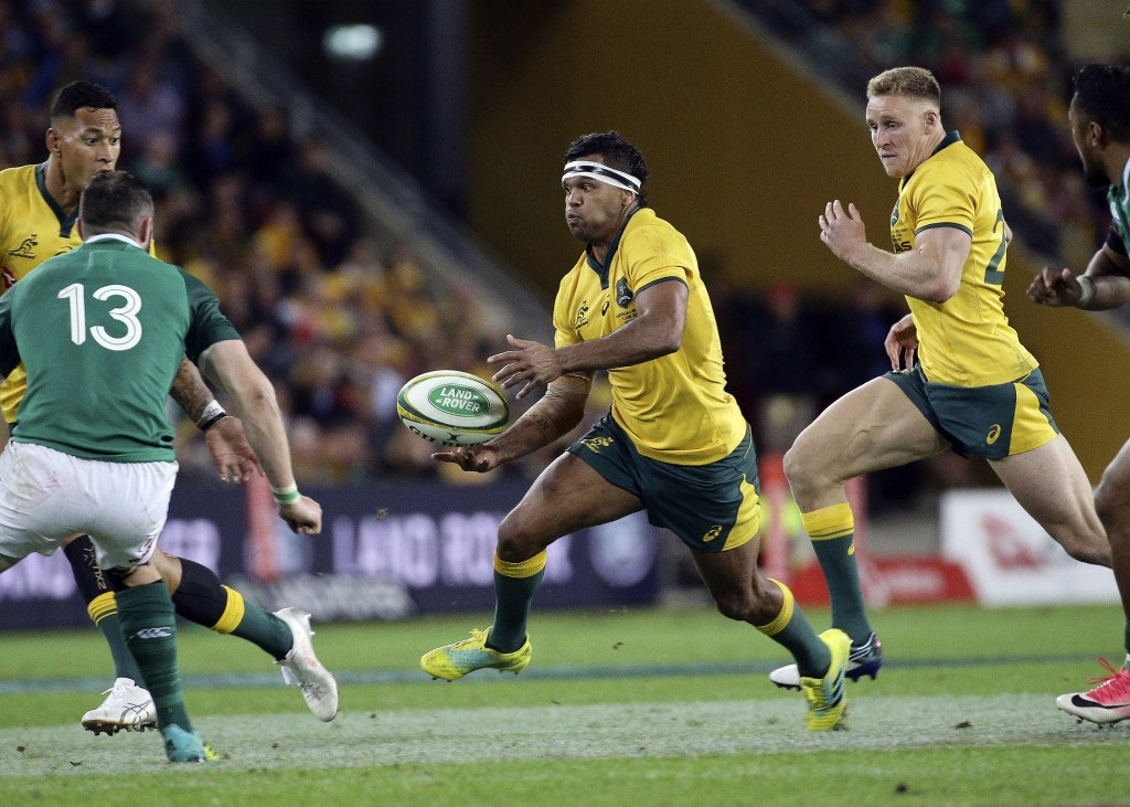 Kurtley Beale of Australia, center, attacks during the International rugby match between Australia and Ireland in Brisbane, Australia, Saturday, June