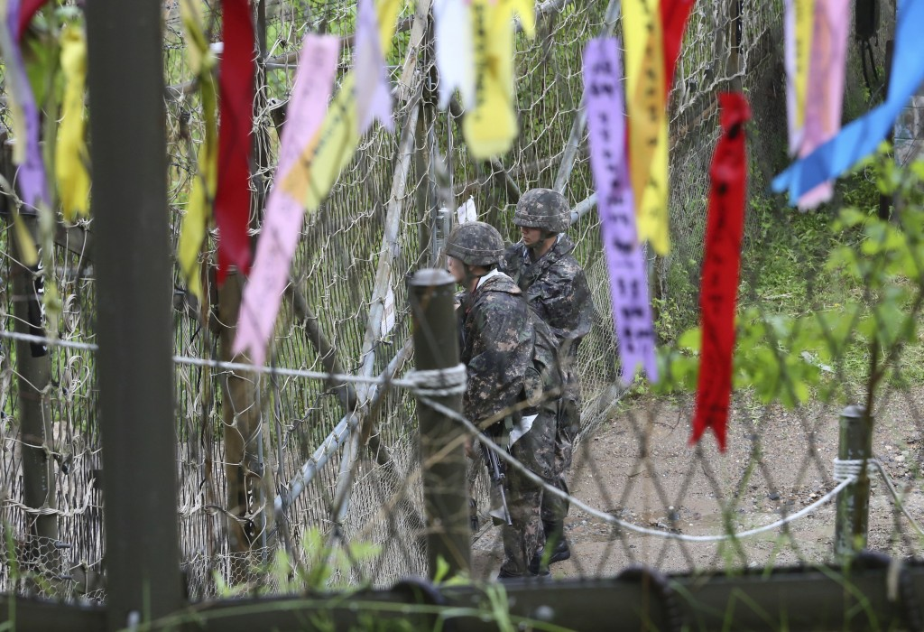 FILE - In this May 16, 2018 file photo, South Korean army soldiers look toward North's side as ribbons hanging on a wire fence wishing for the reunifi...