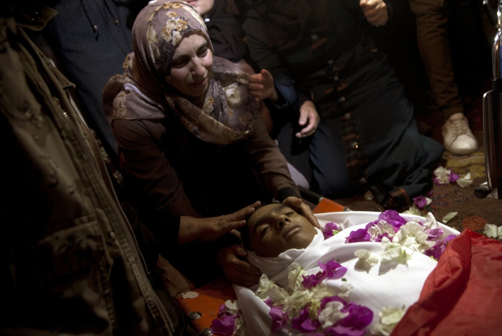 Relatives of 15-year-old Haitham al-Jamal, mourn over his body at the family house during his funeral in Rafah refugee camp, southern Gaza Strip, Satu