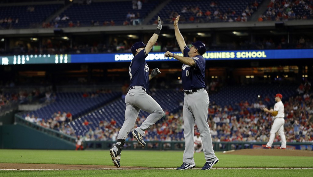 Milwaukee Brewers' Ryan Braun, left, and third base coach Ed Sedar, center, celebrate after Braun's two-run home run of Philadelphia Phillies relief p...