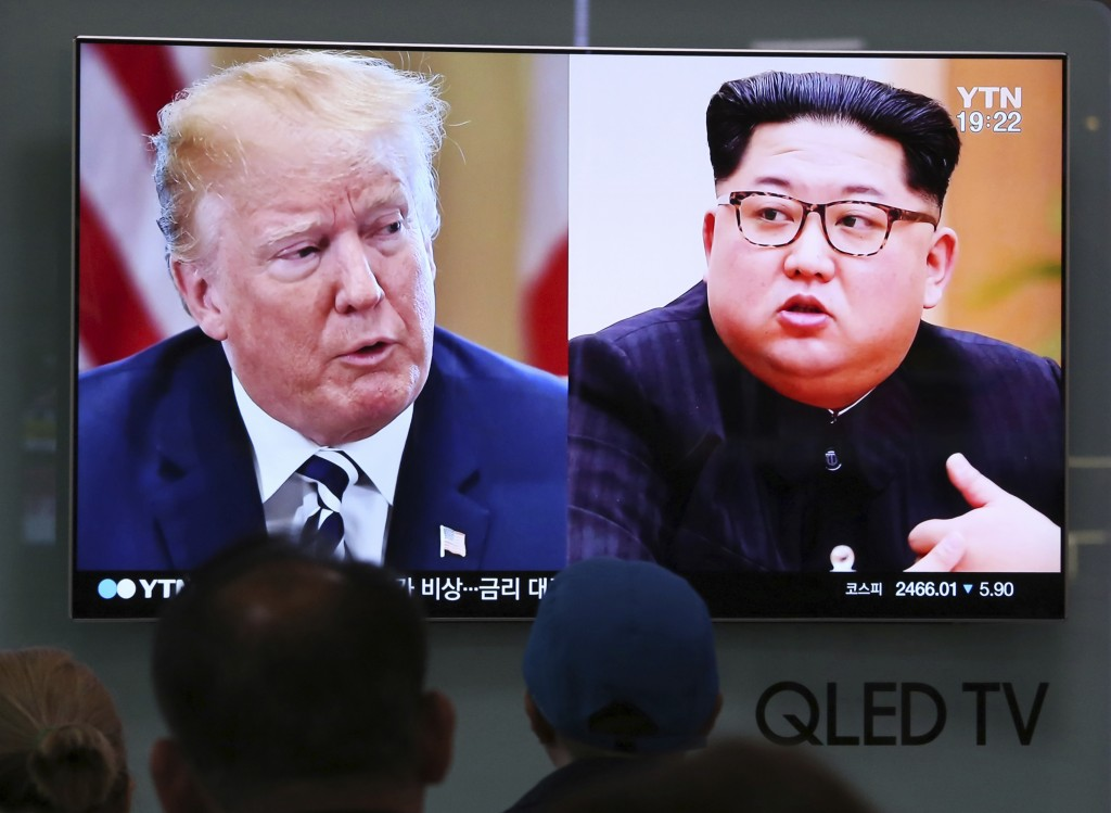 FILE - In this May 24, 2018, file photo, People watch a TV screen showing file footage of U.S. President Donald Trump, left, and North Korean leader K...