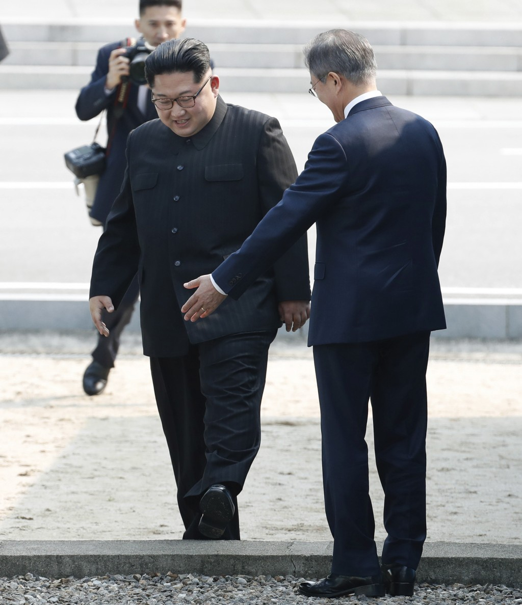 FILE - In this April 27, 2018 file photo, North Korean leader Kim Jong Un, left, crosses the military demarcation line to meet with South Korean Presi...