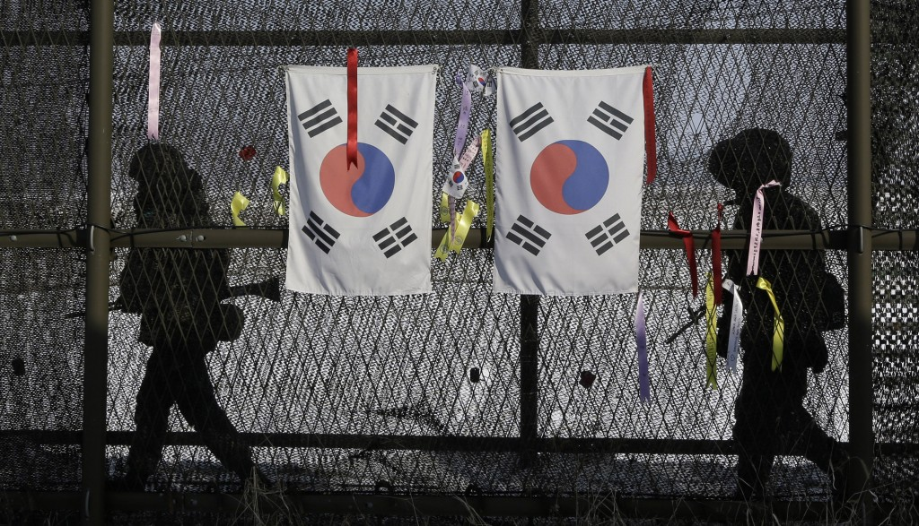 FILE - In this Feb. 13, 2013 file photo, South Korean army soldiers patrol by the national flags and ribbons, wishing for the reunification of the two...