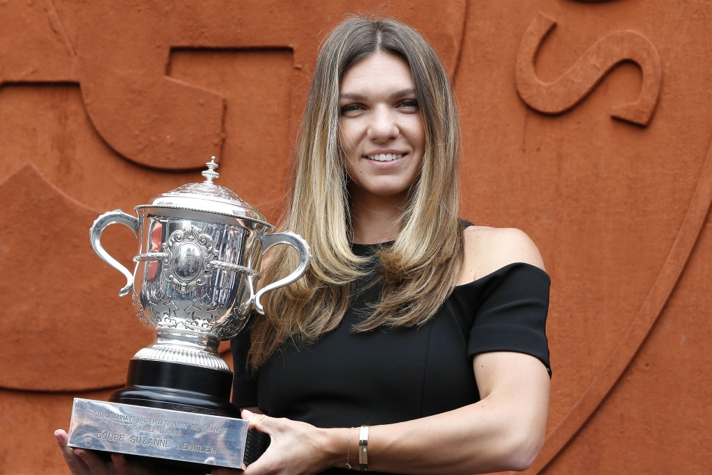 Romania's Simona Halep holds the cup at the Roland Garros stadium, Sunday, June 10, 2018 in Paris. Halep won Saturday the French Open tennis tournamen