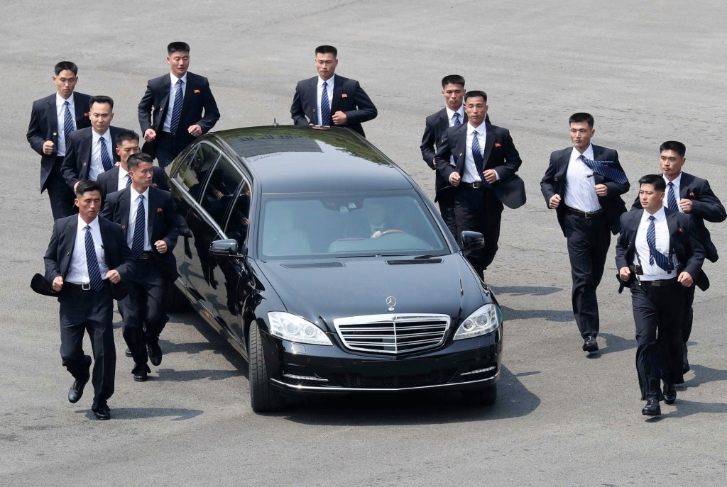 FILE - In this April 27, 2018, file photo, North Korean security persons run by a car carrying North Korean leader Kim Jong Un return to the North sid...