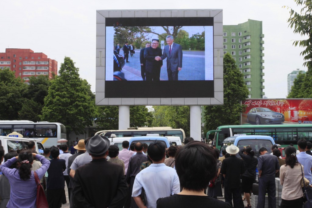 People watch a large screen at the main train station airing video of North Korean leader Kim Jong Un being greeted by Singapore Prime Minister Lee Hs...