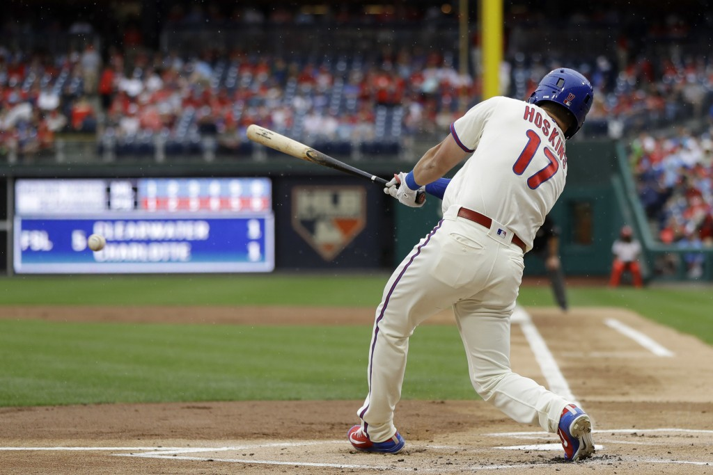 Philadelphia Phillies' Rhys Hoskins follows through after hitting a run-scoring ground-out during the first inning of a baseball game against the Milw...