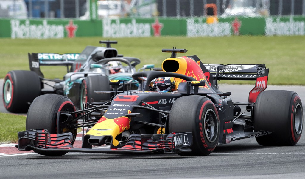 Red Bull Racing driver Daniel Ricciardo of Australia takes a turn at the Senna corner ahead of Mercedes driver Lewis Hamilton of Britain during