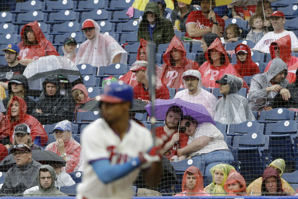 A couple snuggles under an umbrella during a rain shower as Philadelphia Phillies' Nick Williams bats during the fourth inning of a baseball game agai...
