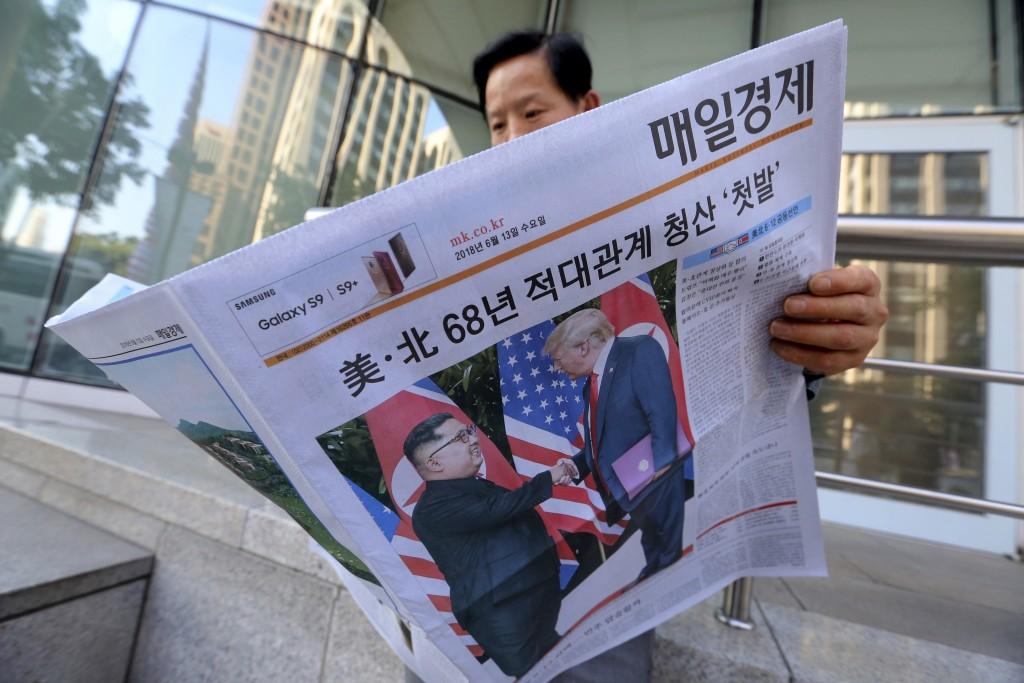 A man reads a newspaper reporting the summit between U.S. President Donald Trump and North Korean leader Kim Jong Un, at a newspaper distributing stat...