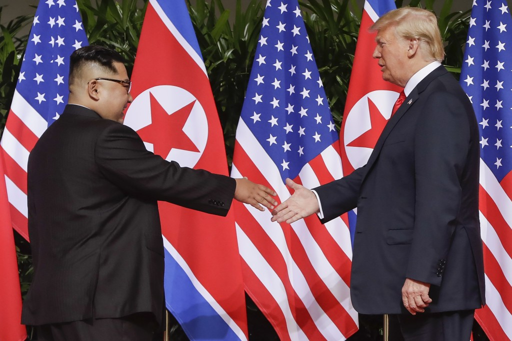 U.S. President Donald Trump reaches to shake hands with North Korea leader Kim Jong Un at the Capella resort on Sentosa Island Tuesday, June 12, 2018