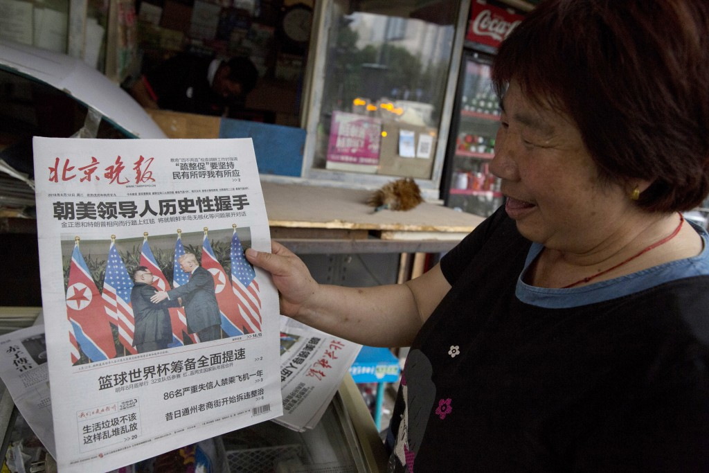 A newspaper vendor holds up a front page photo of the meeting in Singapore between U.S. President Donald Trump and North Korean leader Kim Jong Un at