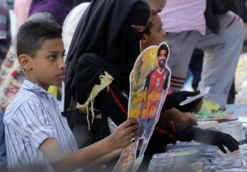 FILE- In this May 16, 2018 file photo, a boy buys a Ramadan decoration depicting the Egyptian Liverpool soccer player Mohamed Salah in Sayyeda Zeinab