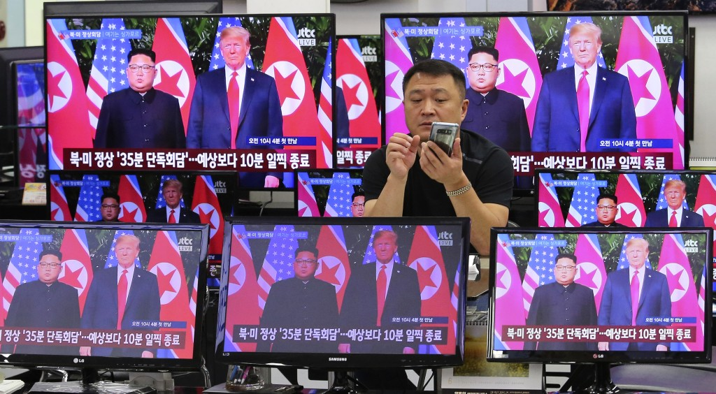In this Tuesday, June 12, 2018, file photo, TV screens show U.S. President Donald Trump, right, meeting with North Korean leader Kim Jong Un in Singap