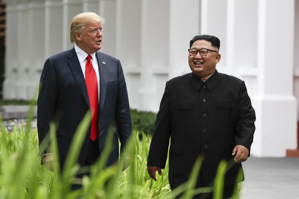 U.S. President Donald Trump and North Korea leader Kim Jong Un walk from their lunch at the Capella resort on Sentosa Island Tuesday, June 12, 2018 in...